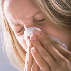Eine Frau niest in ein Taschentuch.