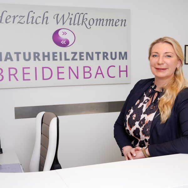 Frau Breidenbach-Klose steht an der Rezeption