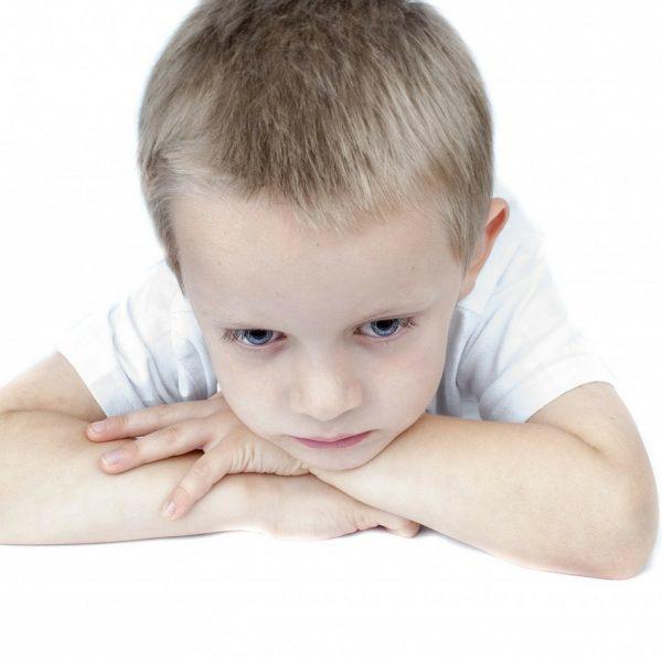 Deprimiertes Kind, das traurig an einem Tisch sitzt