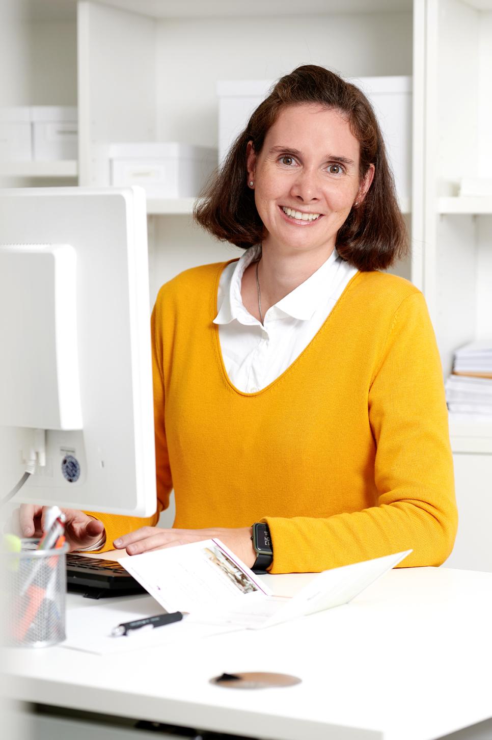 Frau Jürgens vom Naturheilzentrum Breidenbach steht an einem Schreibtisch