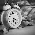 Almodischer Wecker steht auf einer Bettdecke. Thema Schlafmangel
