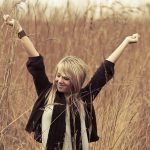 Junge Frau steht auf einem Feld und reckt die Arme in die Höhe