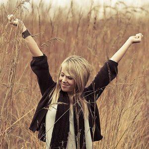 Junge Frau steht in einem Weizenfeld und reckt die Arme in die Höhe