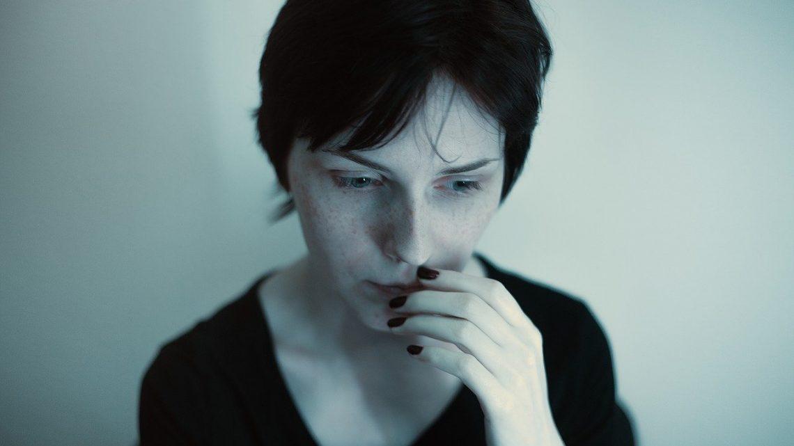 eine junge Frau sitzt gedankenverloren in einem Raum
