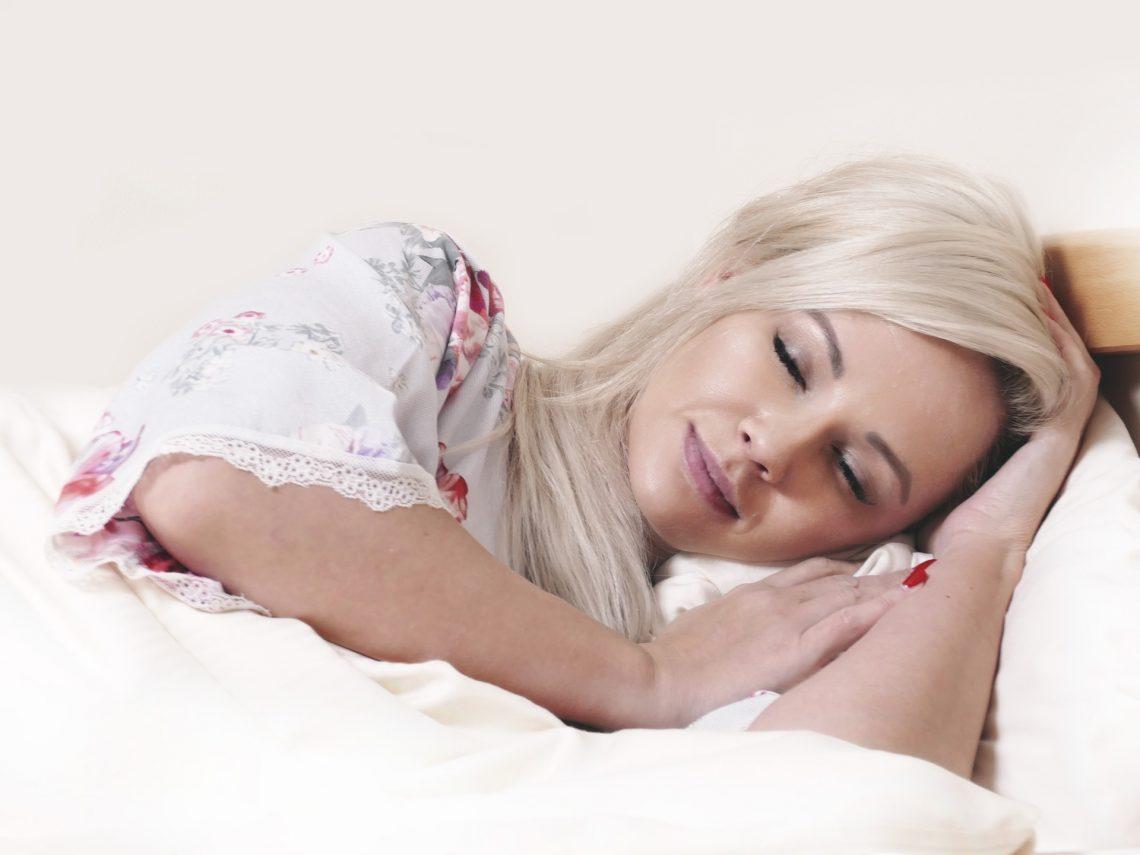 Blonde Frau liegt im Bett und schläft