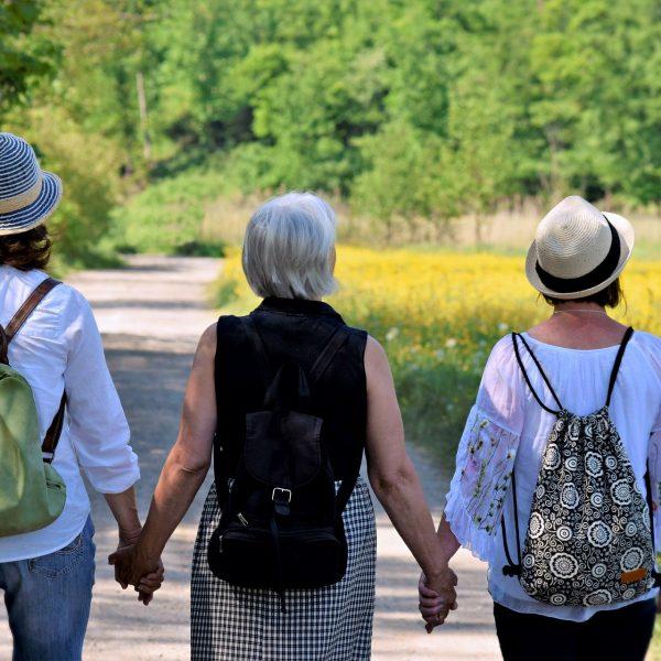 Drei Frauen gehen Hand in Hand im Sommer spazieren
